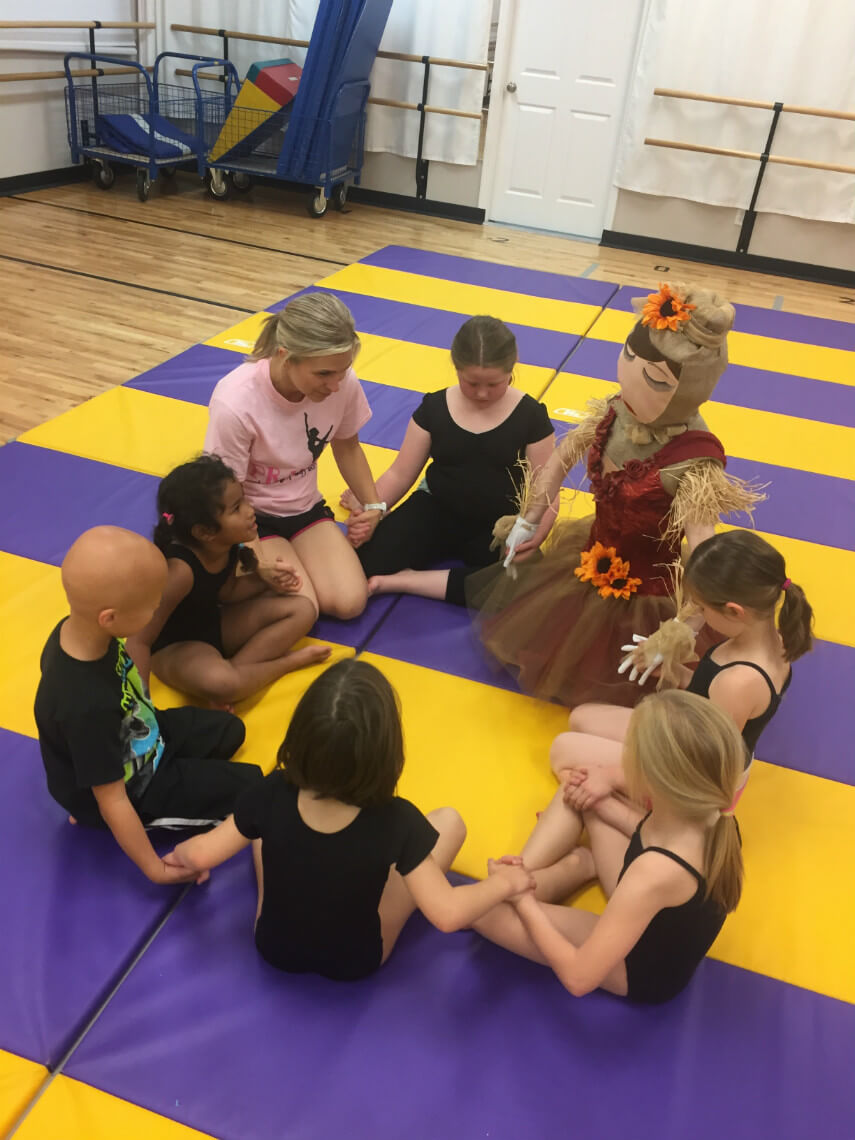 Scarecrow praying with kids in Tumbling class